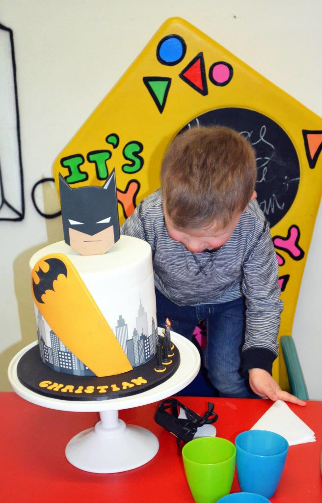 Birthday boy blowing out his Batman cake candles